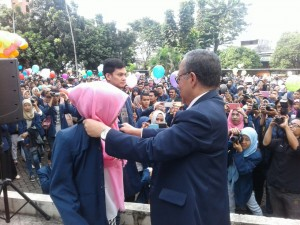 Rektor UIN Jakarta Prof Dr Dede Rosyada mengenakan jaket almamater secara simbolis kepada dua mahasiswa pada acara pelepasan kuliah kerja nyata (KKN) regular di Lapangan Student Center, Senin (25/7). KKN diikuti 2.812 mahasiswa dan akan berlangsung selama 30 hari pada 26 Juli-26 Agustus 20017 di wilayah Tengerang, Tangerang Selatan, dan Bogor. (Foto: Nanang Syaikhu)