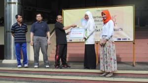 Wakil Rektor Bidang Pengembangan Lembaga dan Kerja Sama Prof Dr Murodi secara simbolis menyerahkan beasiswa pendidikan dari Social Trust Fun (STF) senilai total Rp 119.970.000 kepada 35 mahasiswa di depan gedung Auditorium Harun Nasution tahun 2015 lalu. (Foto: Istimewa)